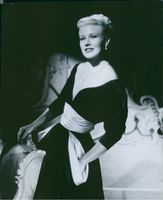 Ginger Rogers standing beside of the sofa while posing.