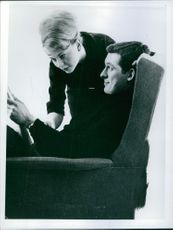 A man sitting on a chair and a woman standing beside him, reading a book.