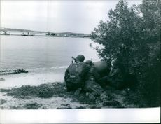 1961  A photo of soldiers hiding and aiming their gun and firing in the seashore.