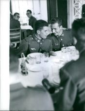 Don Juan Carlos having discussion with a military man at dinning table.