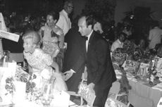 Aga Khan (IV) pulling chair for the lady.