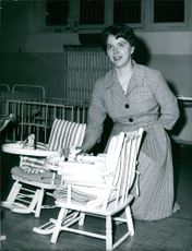 A woman sitting by small chairs for babies.