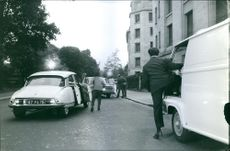 Vintage photo of men escorting Mrs. Madeleine Dassault getting off from her car, days after she was found from her kidnapping. Photo taken on May 26, 1964.
