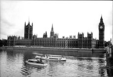 Black and white photograph on London Parliament, Big Ben and boats lying on the water outside.