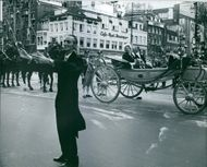 Queen Juliana of the Netherlands passes by behind the conductor.