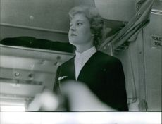An air hostess standing in the flight and looking away.
