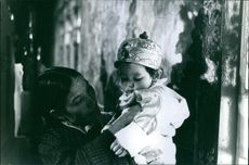 An old woman holding a baby.