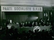 Gaston Defferre in a formal meeting with other politicians.