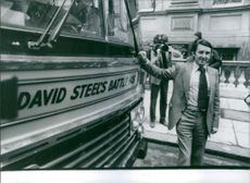 """David Steele poses with the """"Battle Bus""""."""