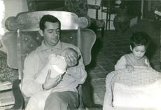 Serge Reggiani lifted up a baby in his arms and looking at him.