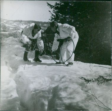 Norwegian soldiers fixing the traps in snow, 1940.