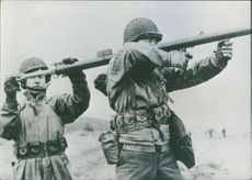 Two American soldiers demonstrating on how to use the bazooka.