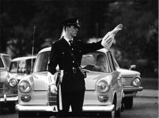 Policeman directs traffic with signs that many do not understand, shows a study of the transition from left to right traffic