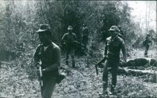 Soldiers in forest during wartime.