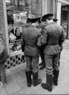 Soviet soldiers in Wittenberg, outside shop like signs with Luther puzzles, Lutheran medals, Lutheran postcards, Luther boards, etc.
