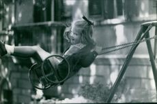 Princess Alexia of Greece and Denmark is playing the swing.
