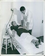Ann Sheridan is giving her blood. Dr. H.W. Watson supervises.
