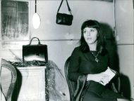 Nicoletta sitting alone and looking the bag hanging. 1967