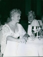 Woman and man sitting in restaurant, woman looking at someone.