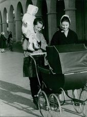 Child sitting on Queen Paola of Belgium's shoulder and another woman pushing go cart.