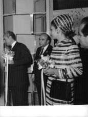 Mohammad Reza Shah Pahlavi with his wife talking to someone in a public ceremony.