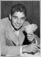 Mexican tennis player Pancho Gonzales with dollar bills in his hand