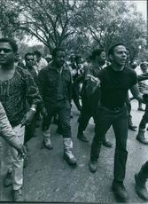 Year ?  A photo of men demonstrators walking on the road.