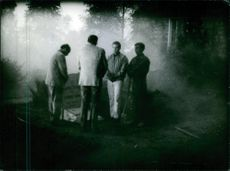 Men standing beside the tomb in the forest.