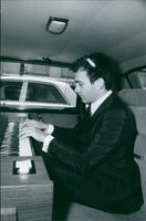 Claude Kahn siting in the car and playing piano. Photo taken on March 20, 1969.