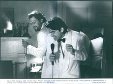 """David (Peter Gallagher, right) and Paul (Bruce Altman) particcipate  in theor traditional Karaoke singing during a fmaily gathering on Nantucket Island in Triump Films' romantic drama """"To Gillian on Her 37th Birthday"""" 1996"""