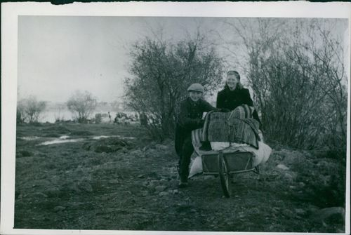 A photo of a woman pushing a wheel barrow carrying their things while a boy assist. 1944