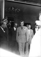 Mohammad Reza Shah Pahlavi walking together with his staff.