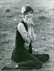 Linda Morand sitting on the grass, smiling.