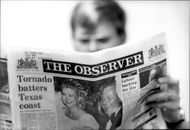 """A man reads the British news magazine """"The Observer"""""""