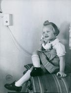 Vintage photo of a young girl gleefully answering the phone.