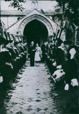 Man and woman receiving guard of honour and smiling.