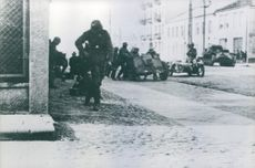 Soldiers running in the street with their tanks and armed vehicles.