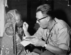 An army doctor give a child a medicine, in Kongo, 1961.