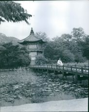 Woman sitting on bridge over lake, pagoda in background.