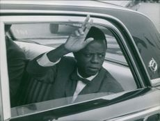 Joseph Iléo, Prime Minister of Congo, waving his hand while inside the car. 1960.