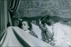 Catherine Diamant lying in bed in covers with a man looking at her.