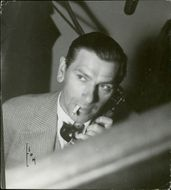 Actor Gustav Edvin Adolphson listening over the telephone while smoking a cigarette.