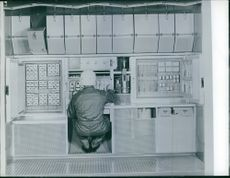 A worker is taking a reading from the control board, 1961.