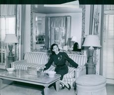 Rosalind Russell sitting on couch in her house and looking at something.