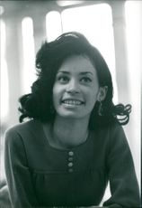 Portrait of a woman smiling while looking away.