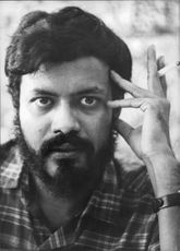 Rajat Neogy in a portrait, holding a cigarette between his fingers.
