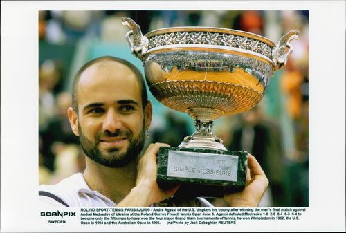 Andre Agassi proudly shows the cup after the win during the US Open.