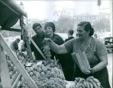 Tina Louise buying grapes with man, woman packing for her. 1960