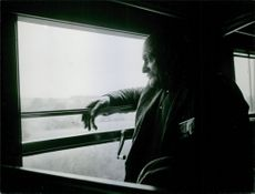 Man travelling in a vehicle and looking outside of the window of the vehicle.
