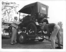 People carrying Ford Model T in an another vehicle.